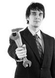 Elegant le affärsman som ut räcker hammaren och skiftnyckeln Royaltyfri Fotografi