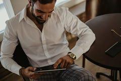 Elegant le man som ser minnestavlan i ett kafé royaltyfria foton
