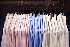 Stylish light-colored blouses on hangers. Elegant light blouses hanging on metal rack in modern clothes shop royalty free stock photo