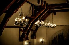 Elegant light chandeliers in dark ballroom. Elegant light chandelier in ballroom on ceiling with wooden elements. Architecture, decor design concept stock photography