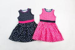 Elegant light children summer dresses. Pink and black on white dots Stock Photography
