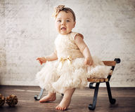 Elegant little girl on the tiny bench Stock Photography