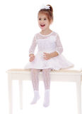 Elegant little girl in a white dress sitting on Stock Photography