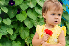 Elegant little girl in yellow dress with red poppy flower Stock Photography