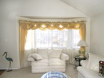 Elegant living room. Elegant, well furnished living room with white furniture and bay window Royalty Free Stock Images
