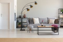 Elegant living room with grey sofa with patterned pillows, wooden coffee table and industrial lam, with. Elegant living room with grey sofa with patterned royalty free stock images