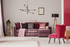 Elegant living room interior. Copper table near violet corner sofa and red armchair in elegant living room interior with mockup stock images