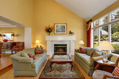 Elegant living room interior. Gray sofas with red pillows and white fireplace create comfort Stock Images
