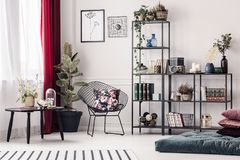 Living room with metal rack. Elegant living room interior with metal armchair standing between a window and a metal rack with decorations royalty free stock photo
