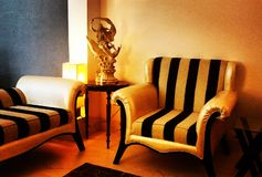 Elegant Living Room. Warm golden lighting surrounds this corner of a living room with furniture designed in black and white stripes Royalty Free Stock Photo
