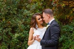 Elegant lockig brud och stilfull brudgum Arkivfoto