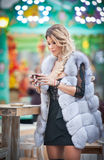 Elegant long fair hair young beautiful woman with white fur coat, outdoor shot in a cold winter day. Attractive blonde girl Royalty Free Stock Photography