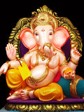Elegant Lord Ganesha. A beautiful elegant idol of lord Ganesha relaxing with dazzling gold jewelery all over him, kept for sale Stock Image