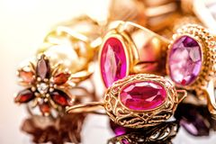 Elegant luxury composition of gold jewelry with ring with red amethyst and ruby gemstone and diamonds on light background close-up. Macro and reflection stock images
