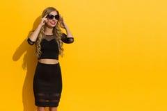 Elegant lycklig kvinna, i att hålla ögonen på för solglasögon arkivbilder
