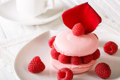 Elegant macaroon with raspberry filling and floral rose petals c Royalty Free Stock Photography