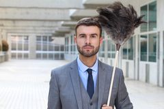 Elegant maid holding feather duster royalty free stock photography