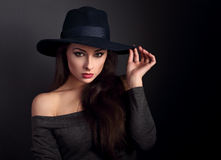 Elegant makeup woman in fashion hat posing on dark shadow backgr Stock Images