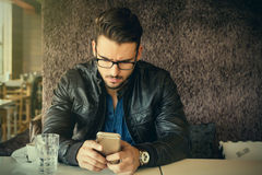 Elegant male with attractive haircut using smartphone Stock Photography