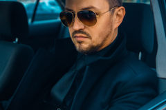 Elegant male in black suit driving car Royalty Free Stock Image
