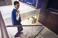 Elegant male. Businessman with a suit on his shoulder walking down the stairs in the mall Stock Images