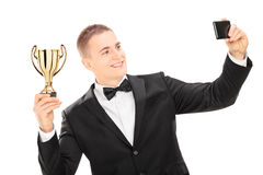 Elegant male holding trophy and taking a selfie. Elegant male holding a trophy and taking a selfie with phone isolated on white background Stock Photos