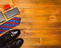 The elegant male set: men`s shoes, leather belt, on the wooden background. The elegant male set: men`s shoes, leather belt, suit, credit card on the wooden Royalty Free Stock Image