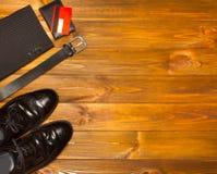 The elegant male set: men`s shoes, leather belt, on the wooden background. The elegant male set: men`s shoes, leather belt, suit, credit card on the wooden Stock Images