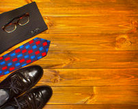 The elegant male set: men`s shoes, suit, tie on wooden background. Royalty Free Stock Image