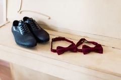 Elegant male shoes and bow-tie on a light brown wooden background.  Stock Photography