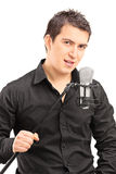 Elegant male singer holding a microphone Royalty Free Stock Photography