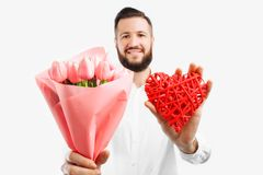Elegant man with a beard, with a bouquet of pink tulips and a red valentine heart, a gift for Valentine`s Day. On a white background stock images