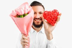 Elegant man with a beard, with a bouquet of pink tulips and a red valentine heart, a gift for Valentine`s Day royalty free stock photo