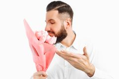 Elegant man with a beard holding a bouquet of tulips, a gift for Valentine`s Day royalty free stock photo