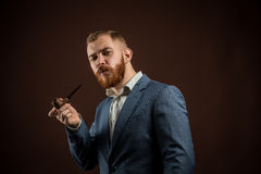 Elegant man with beard holding smoking pipe. Portrait of handsome confident man in suit holding smoking pipe against of brown background.Isolated Stock Photos