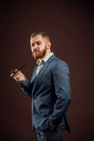 Elegant man with beard holding smoking pipe. Portrait of handsome confident man in suit holding smoking pipe against of brown background.Isolated Royalty Free Stock Photography