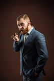 Elegant man with beard holding smoking pipe. Portrait of handsome confident man in suit holding smoking pipe against of brown background.Isolated Stock Photo