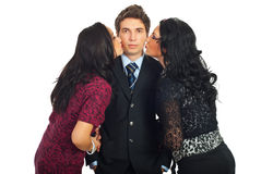 Elegant man being kissed by two women. Elegant serious man in black suit being kissed by to beautiful women isolated on white background Royalty Free Stock Images