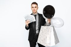 An elegant man, in a black suit, holding bags, for shopping, and stock photo