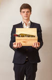Elegant man in black suit holding wooden box with wine Royalty Free Stock Photos