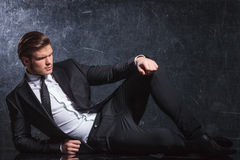 Elegant man in black suit and tie lies down. Fashion elegant man in black suit and tie lies down and looks away from the camera in studio stock photos