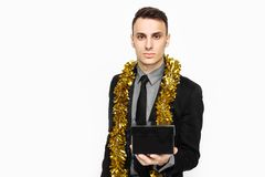 An elegant man in a black suit, and with tinsel on his neck, holding a black case, for decoration, a gift for the holiday, on a wh stock photography