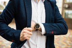 Elegant man in blue suit, business man`s hand with fashion no br. And wrist watch, men fashion and accessories closeup shot royalty free stock photography