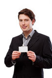 Elegant man with businesscard. A smiling elegant man holding a blank business card for your own text Royalty Free Stock Photo