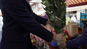 Elegant man buying huge bouquet of flowers hurrying on date to his beloved. Stock footage stock footage