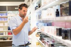 Elegant man choosing perfume in retail store. Casual man testing and buying gift for his lady in a beauty store stock photography