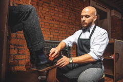 Elegant man cleaning footwear of a client. Bald worker brushing brogues of a man who sitting in front of him Royalty Free Stock Photos