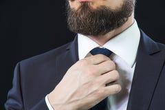 Elegant man correcting his necktie. Stock Images