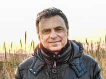 Elegant man with dark padded jacket in the countryside Stock Image