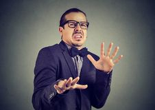 Scared young man feeling disgust. Elegant man doing stop gesture and looking away with disgust and fear royalty free stock image